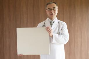 メッセージボードを持ち微笑む医者の写真素材 [FYI04551453]