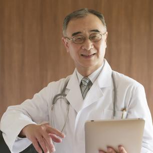 タブレットPCを持ち微笑む医者の写真素材 [FYI04551459]