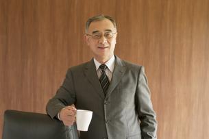 コーヒーカップを持ち椅子に寄りかかるビジネスマンの写真素材 [FYI04551548]