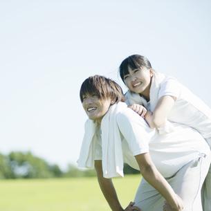 草原でじゃれあうカップルの写真素材 [FYI04551567]