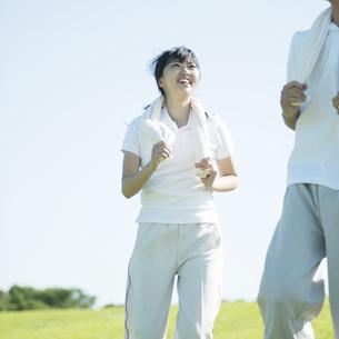 草原でジョギングをするカップルの写真素材 [FYI04551573]