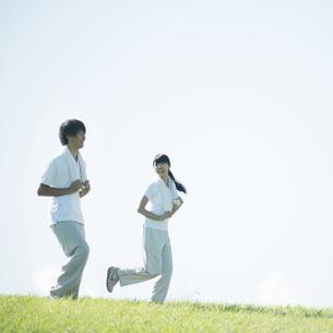 草原でジョギングをするカップルの写真素材 [FYI04551582]