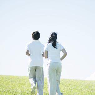 草原を走るカップルの後姿の写真素材 [FYI04551586]