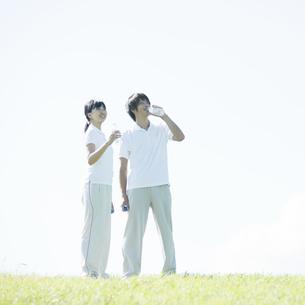 草原で水分補給をするカップルの写真素材 [FYI04551591]