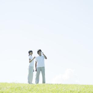 草原で水分補給をするカップルの写真素材 [FYI04551594]