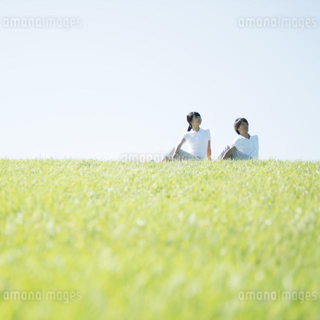 草原でストレッチをするカップルの写真素材 [FYI04551595]