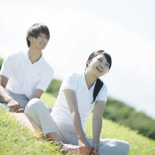草原でストレッチをするカップルの写真素材 [FYI04551598]