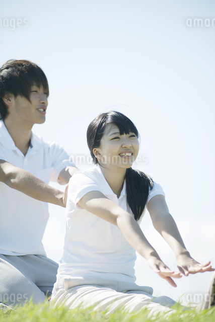草原でストレッチをするカップルの写真素材 [FYI04551602]