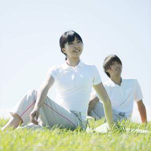 草原でストレッチをするカップルの写真素材 [FYI04551614]