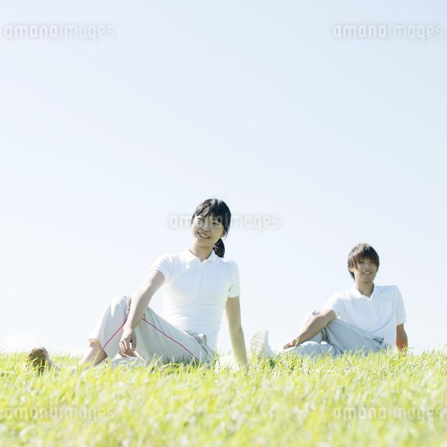 草原でストレッチをするカップルの写真素材 [FYI04551615]