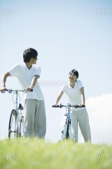 草原で自転車を押すカップルの写真素材 [FYI04551628]