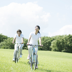 草原で自転車に乗るカップルの写真素材 [FYI04551639]