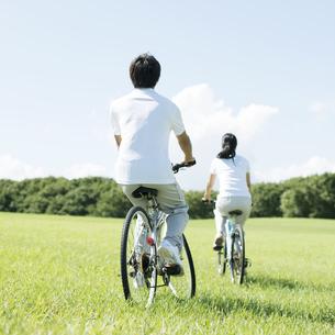 草原で自転車に乗るカップルの後姿の写真素材 [FYI04551642]