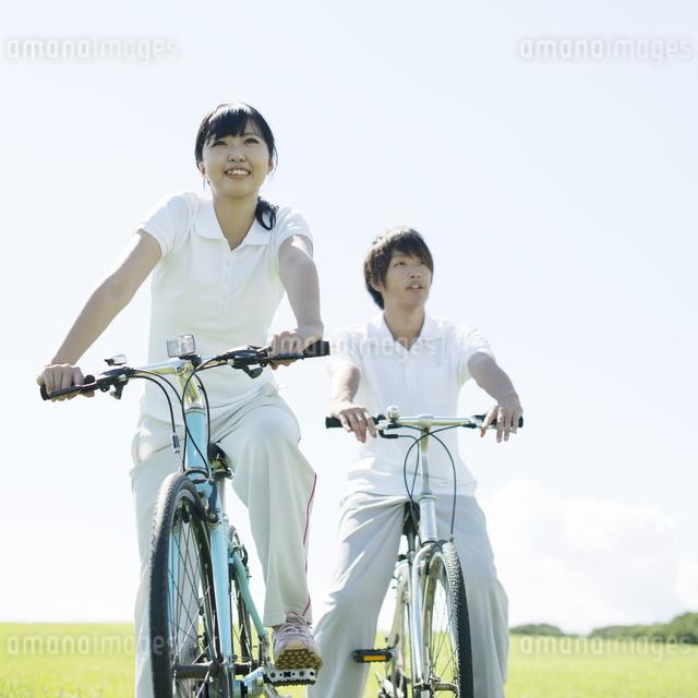 草原で自転車に乗るカップルの写真素材 [FYI04551644]