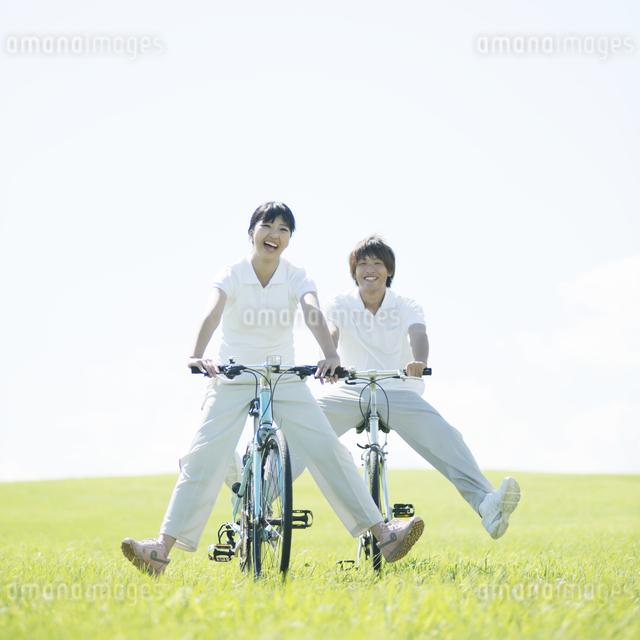 草原で自転車に乗るカップルの写真素材 [FYI04551648]