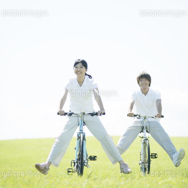 草原で自転車に乗るカップルの写真素材 [FYI04551650]