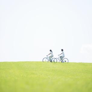 草原で自転車に乗るカップルの写真素材 [FYI04551654]