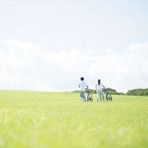 草原で自転車を押すカップルの写真素材 [FYI04551677]