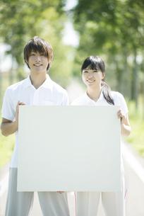 一本道でメッセージボードを持つカップルの写真素材 [FYI04551708]