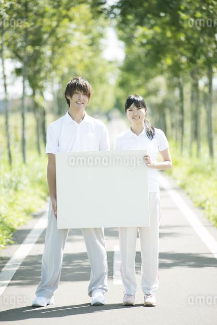 一本道でメッセージボードを持つカップルの写真素材 [FYI04551710]