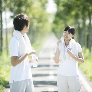 一本道で水分補給をするカップルの写真素材 [FYI04551720]