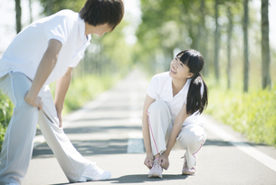 靴紐を結び直す女性と準備運動をする男性の写真素材 [FYI04551721]