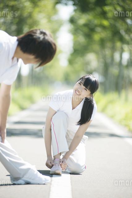 靴紐を結び直す女性と準備運動をする男性の写真素材 [FYI04551723]