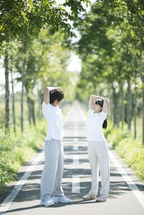 一本道で準備運動をするカップルの写真素材 [FYI04551734]