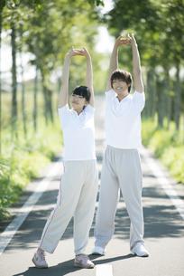 一本道で準備運動をするカップルの写真素材 [FYI04551739]