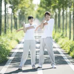 一本道で準備運動をするカップルの写真素材 [FYI04551754]