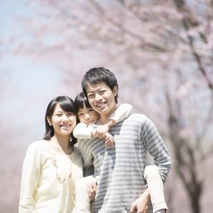桜の前でおんぶをする親子の写真素材 [FYI04551766]
