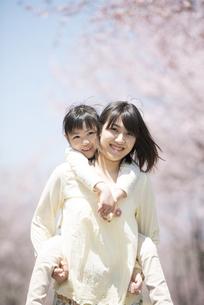 桜の前でおんぶをする親子の写真素材 [FYI04551770]