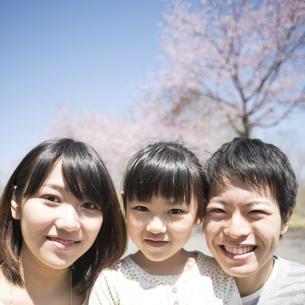 桜の前で微笑む親子の写真素材 [FYI04551826]
