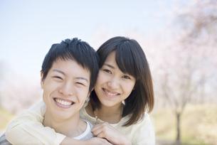 桜の前で微笑むカップルの写真素材 [FYI04551829]