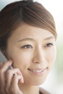 スマートフォンで電話をするビジネスウーマンの写真素材 [FYI04551863]