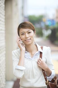 スマートフォンで電話をするビジネスウーマンの写真素材 [FYI04551913]