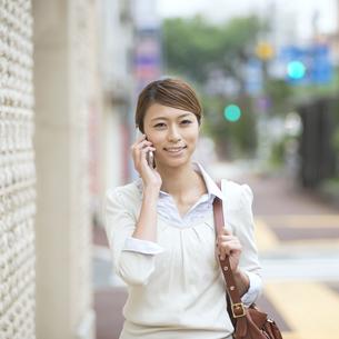 スマートフォンで電話をするビジネスウーマンの写真素材 [FYI04551921]