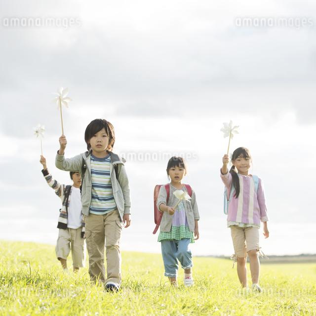 風車を持ち土手を歩く小学生の写真素材 [FYI04551954]