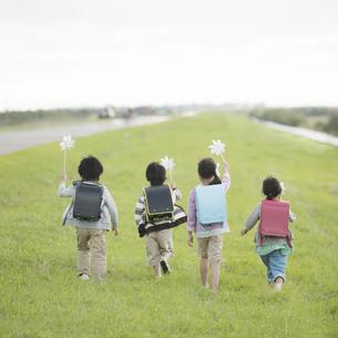 風車を持ち土手を走る小学生の後姿の写真素材 [FYI04551962]