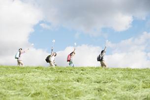 風車を持ち草原を歩く小学生の写真素材 [FYI04551978]