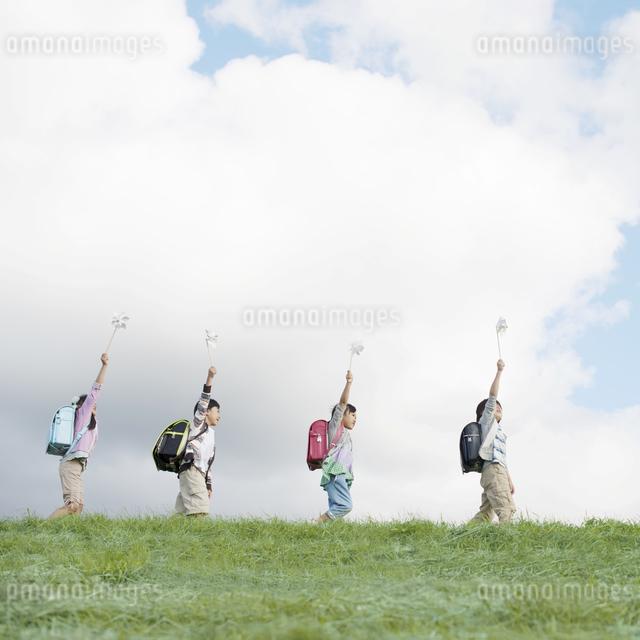 草原で風車を持つ小学生の写真素材 [FYI04551985]