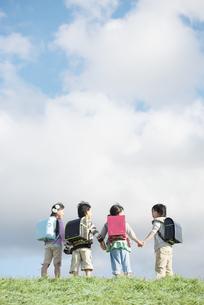 草原で手をつなぐ小学生の後姿の写真素材 [FYI04551998]