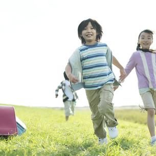 草原を走る小学生の写真素材 [FYI04552000]