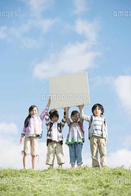 草原でメッセージボードを持ち微笑む小学生の写真素材 [FYI04552015]