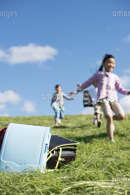 草原に置いてあるランドセルと小学生の写真素材 [FYI04552031]