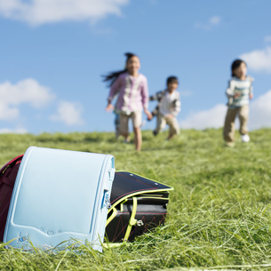 草原に置いてあるランドセルと小学生の写真素材 [FYI04552032]