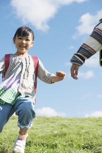 草原を走る小学生の写真素材 [FYI04552036]