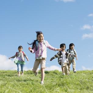 草原を走る小学生の写真素材 [FYI04552044]
