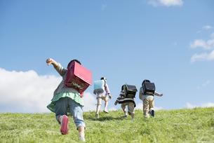草原を走る小学生の後姿の写真素材 [FYI04552045]