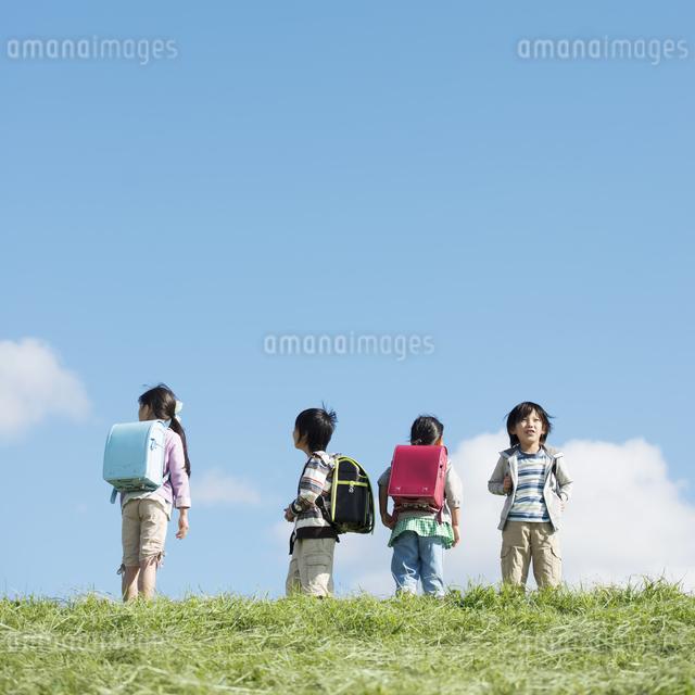 草原に立つ小学生の写真素材 [FYI04552055]